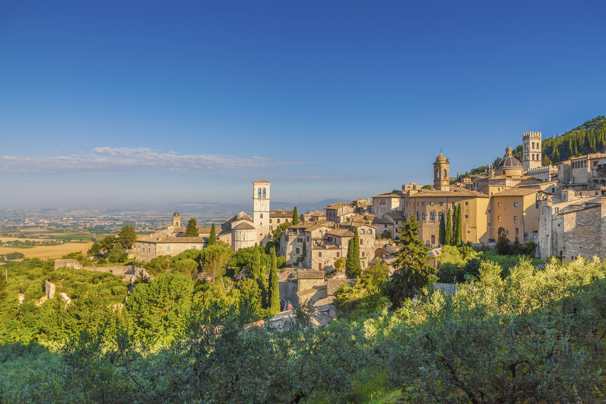 Panoramic view of the historic town of Assisi in beautiful golden morning light at sunrise in summer, Umbria, Italy